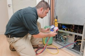furnace technician repairs a furnace and air conditioning