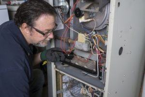 furnace repairman diagnosing a problem with the HVAC system